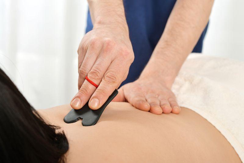massage therapist using gua sha tool on patient's upper back