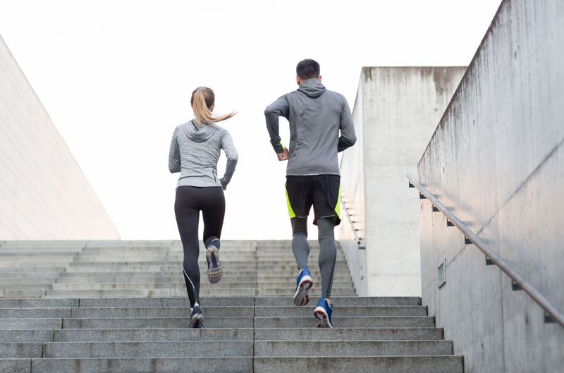 man and woman running jogging up outdoor stairs