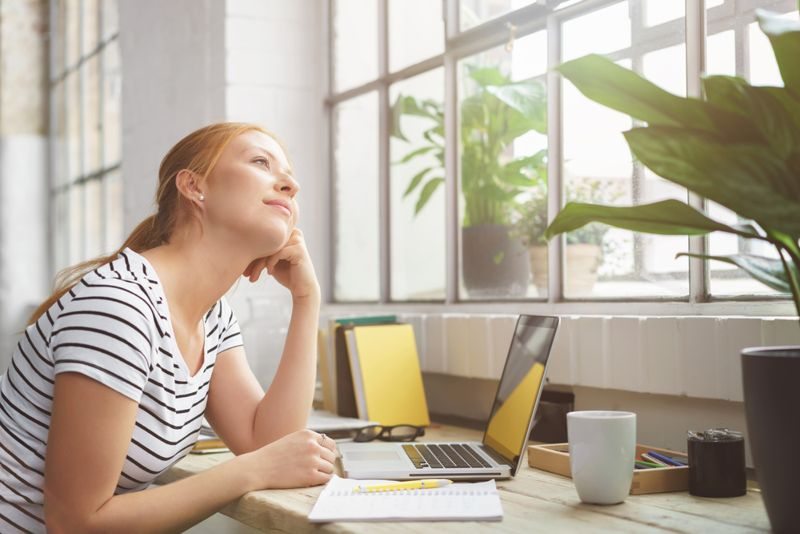 young woman at work desk staring off into space
