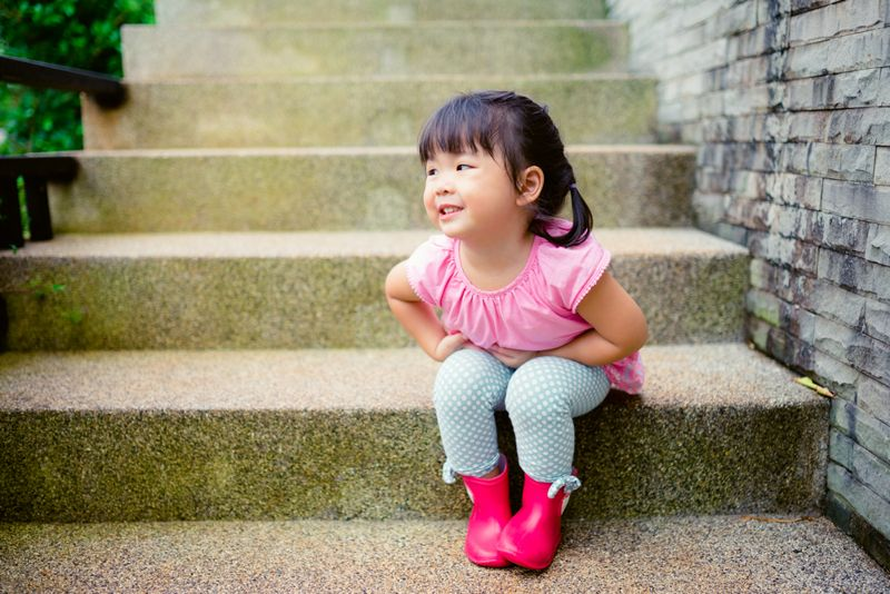 toddler girl on steps needs to use the bathroom