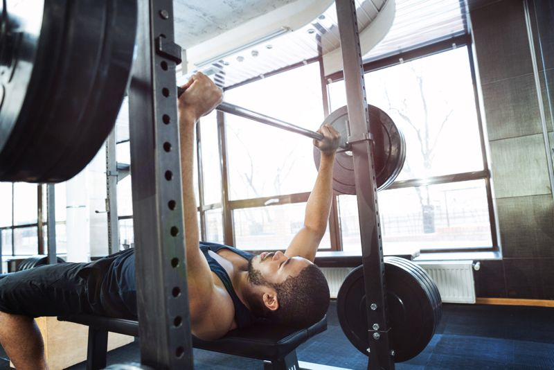 man doing a standard bench press at the gym