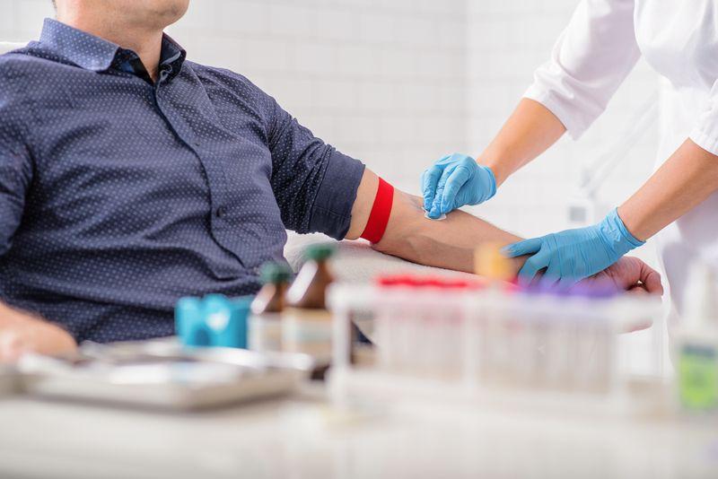 man having blood taken by a nurse in blue gloves