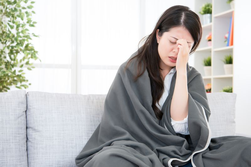 sad, unwell woman wrapped in a blanket