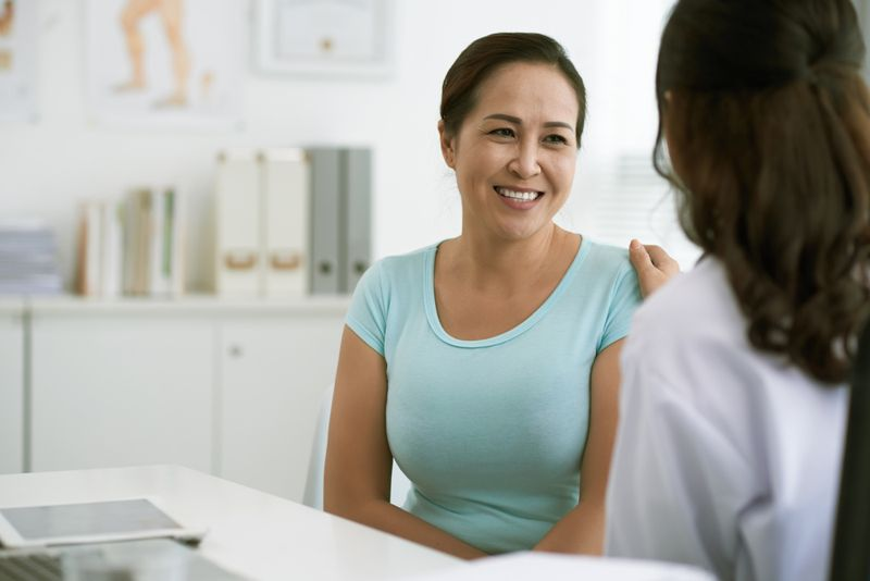 smiling woman talking with her doctor