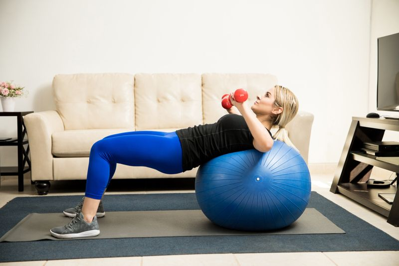 woman doing a bench press with dumbbells on a stability ball