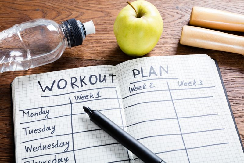 workout plan concept notebook and healthy foods