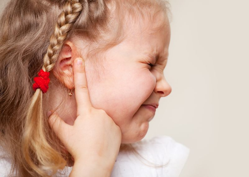 toddler girl with an ear ache, in pain