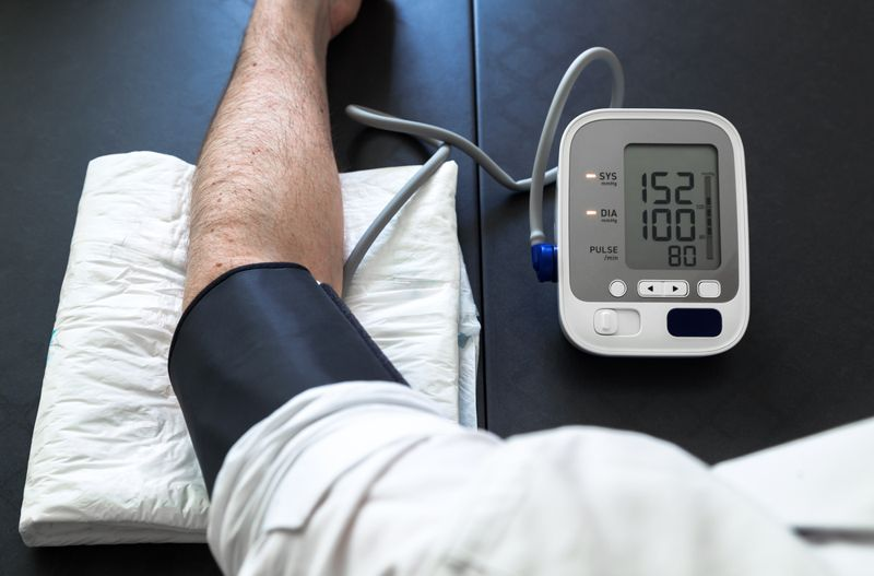 cropped image of man wearing blood pressure cuff, high blood pressure concept