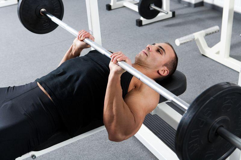 man doing a bench press with a narrow grip