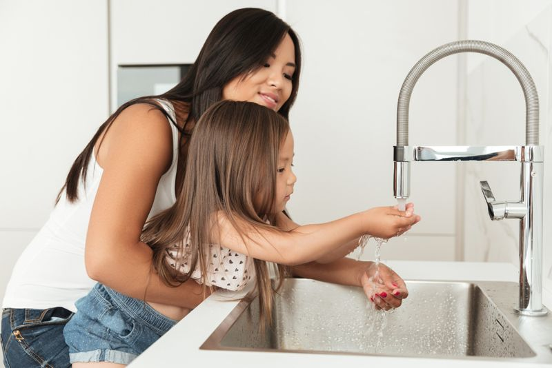 mom helping her young daughter wash her hands