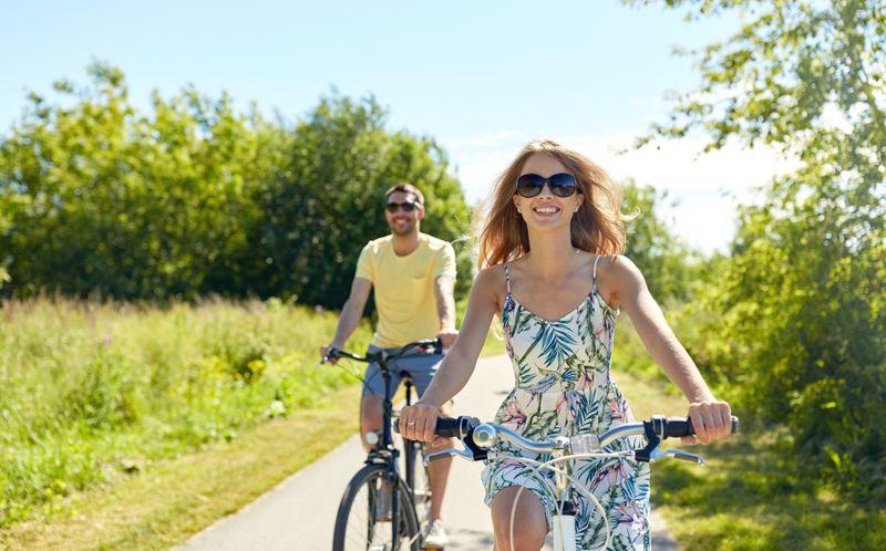 young couple smiling biking along nature trail