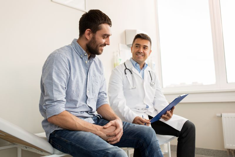 smiling man and doctor talking in clinic