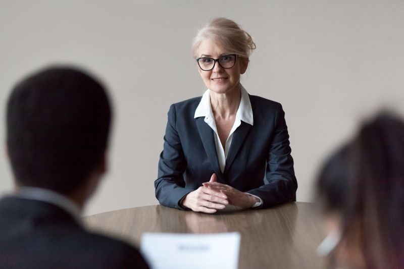 Smiling middle aged senior female job applicant listening to hr questions making first impression at interview, recruiters interviewing older mature candidate, recruitment, age and employment concept