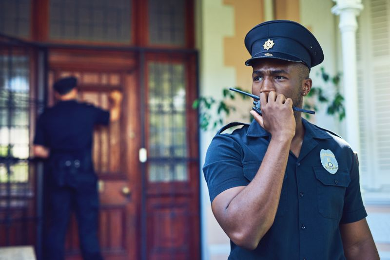 Shot of a law enforcement officer on duty while talking on a walkie talkie in a residential area