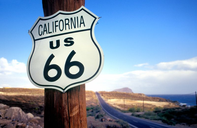 California highway route 66 road sign on wooden pole at clear sky, selective focus on the foreground