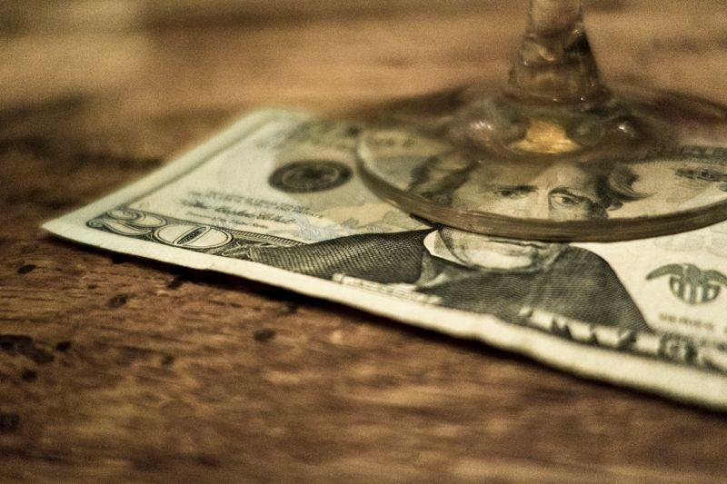 20 dollar bill under a glass in a restaurant.