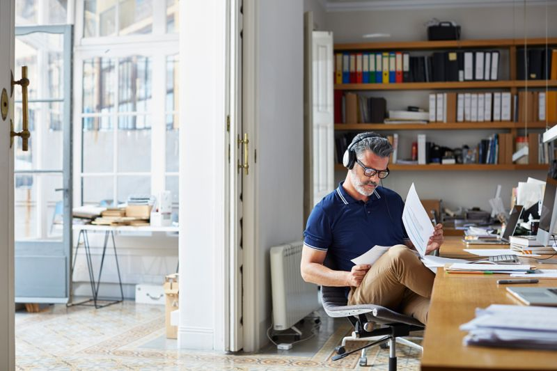 Mature businessman examining documents at desk in office