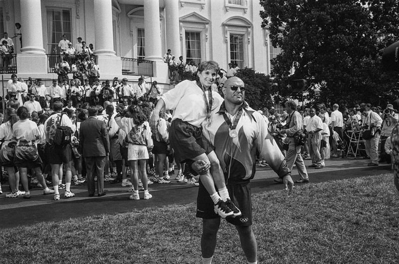 WASHINGTON D.C. - AUG. 7: Gold-metal gymnast Kerri Strug and silver-metal wrestler Matt Ghaffari pose in front of members of the U.S. Olympic Team during a visit to the White House before a group picture with the First Family on August 7, 1996.