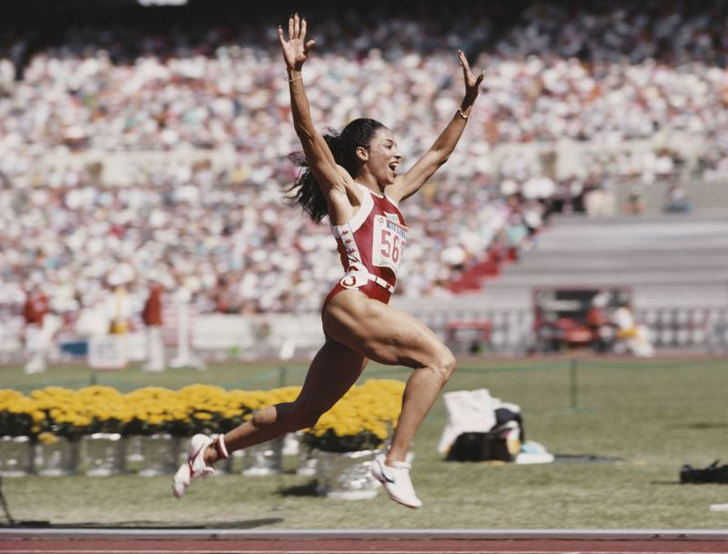 Florence Griffith-Joyner of the United States celebrates winning gold in the Women's 100 metres final event during the XXIV Summer Olympic Games on 25 September 1988 at the Seoul Olympic Stadium in Seoul, South Korea.