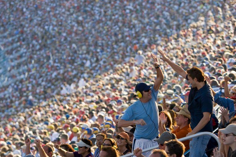 Crowd in stadium watching stock car racing, two men having high-five