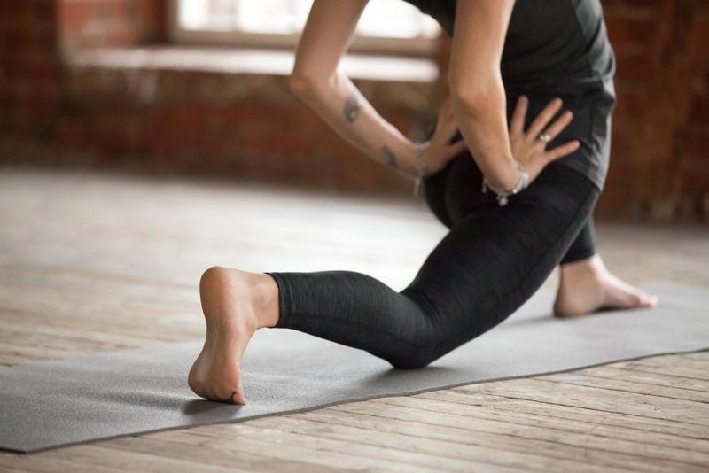 woman doing a hip flexor stretch on yoga mat