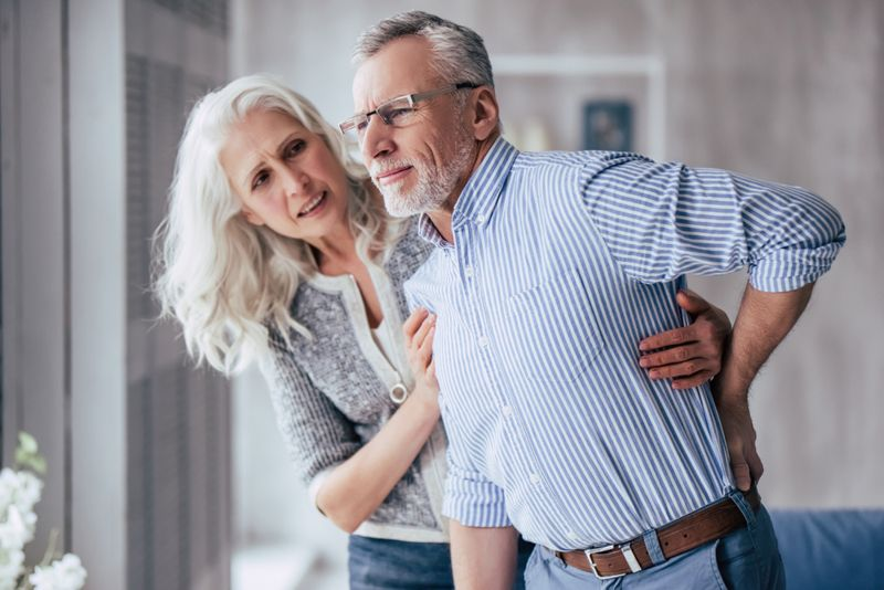 older woman helping husband with back pain stand