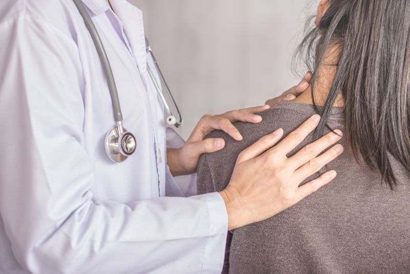 doctor examining patients back or shoulder
