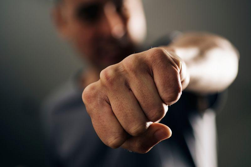 selective focus image of a man punching toward camera