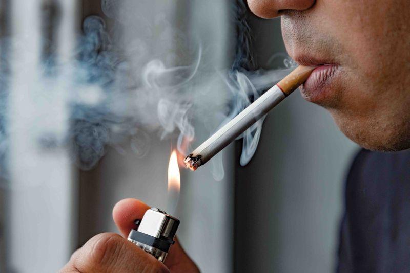 close up of a man lighting a cigarette