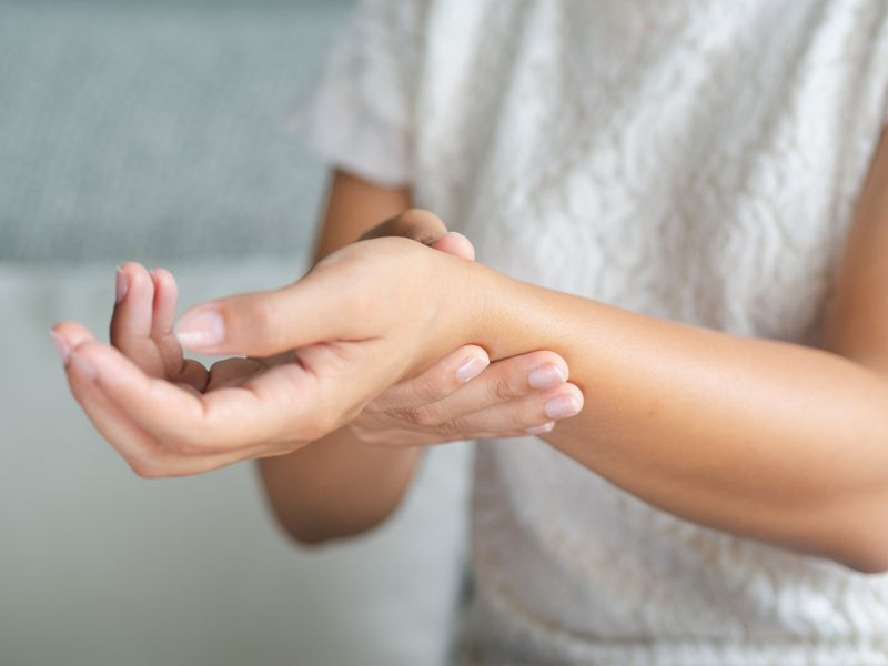 woman holding her sore wrist