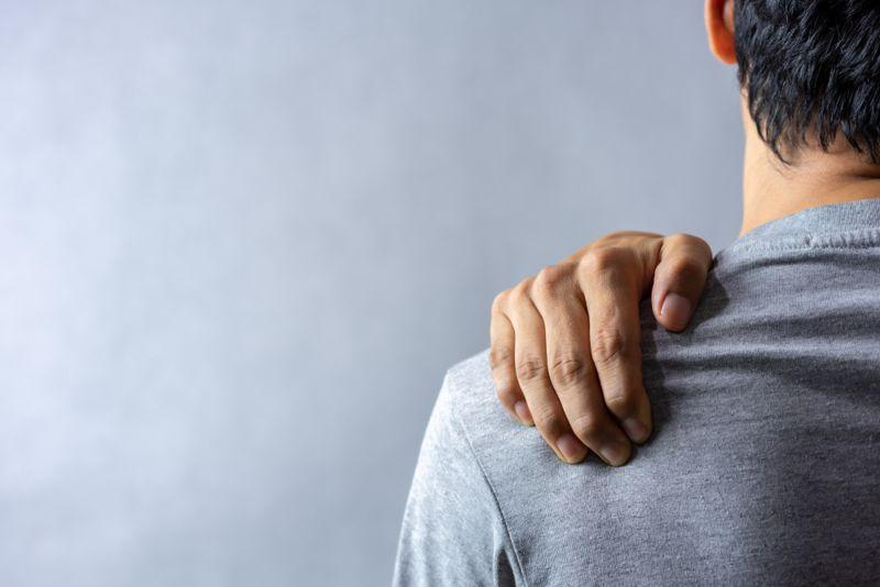 man holding his shoulder; shoulder pain concept