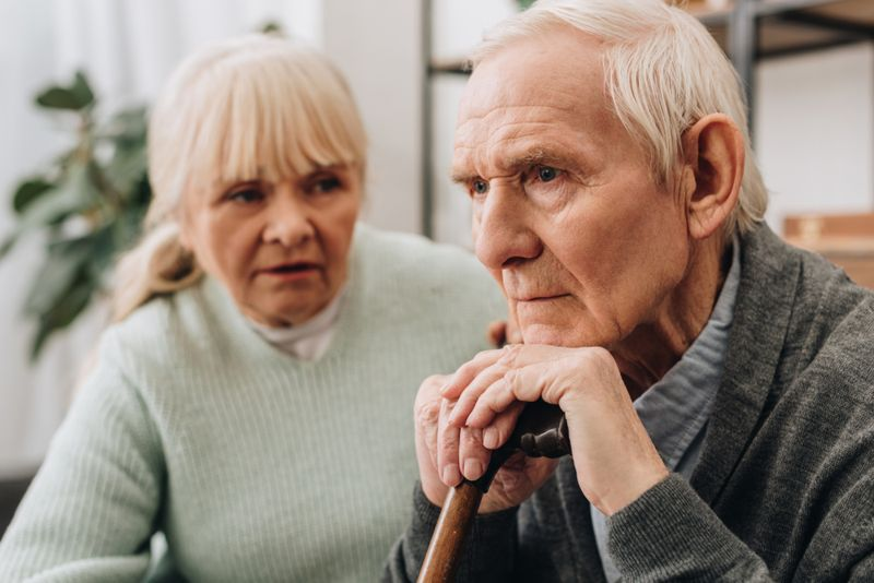 older man looks sad and confused as wife watches
