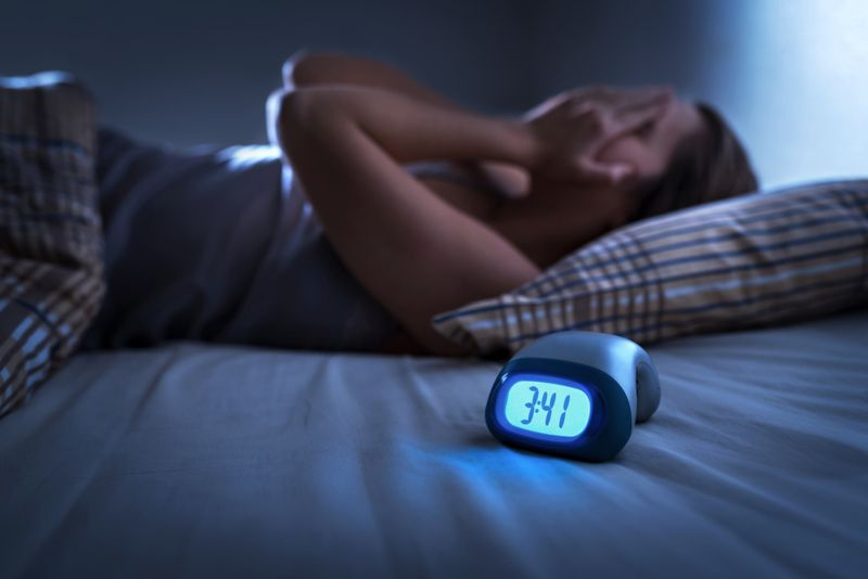 woman in bed in early morning can't sleep