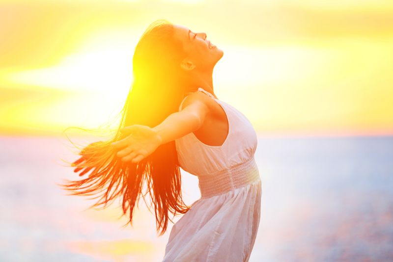 woman with arms outstretched in the sunshine