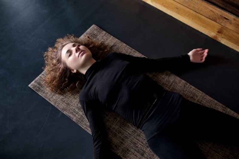 young woman meditating lying on floor