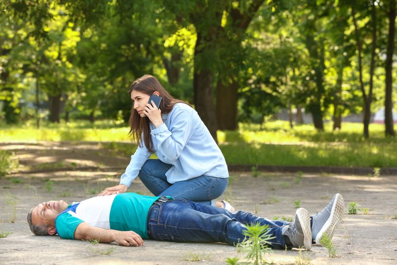 woman calling 911 for an unconscious man