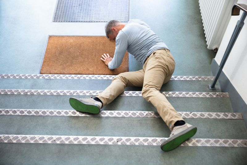 man at bottom of stairs has fallen on his hip