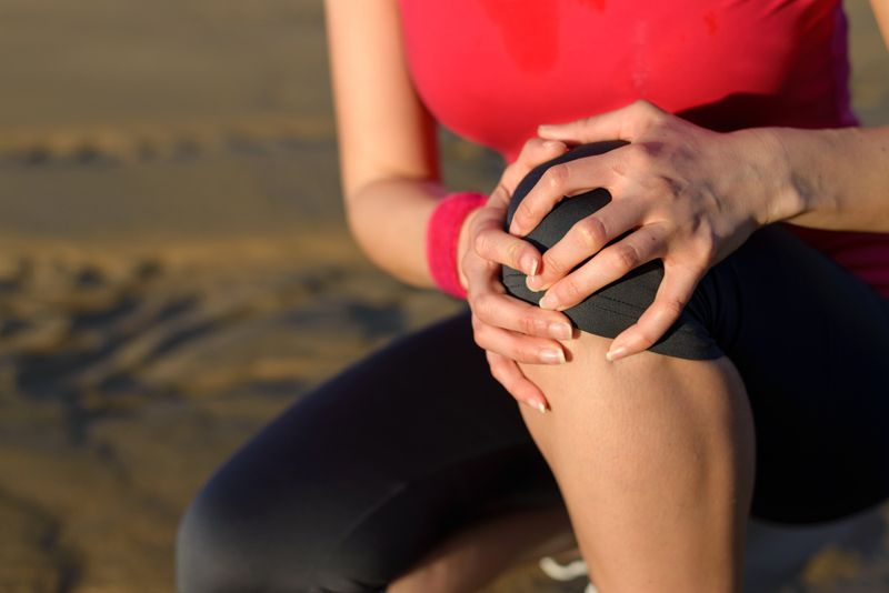 woman holding her knee, knee pain concept