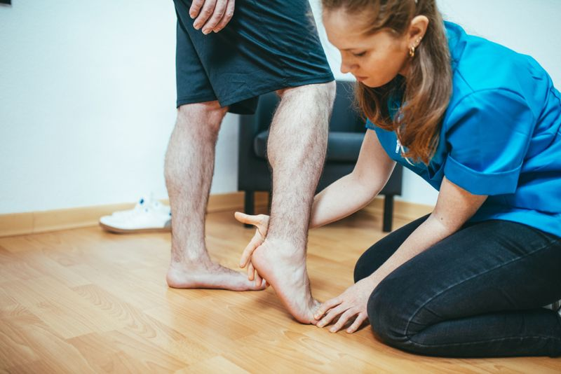 physical therapist checking patient's foot
