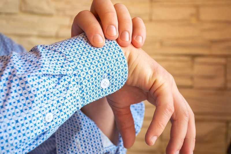 cropped image of a man holding his sore wrist