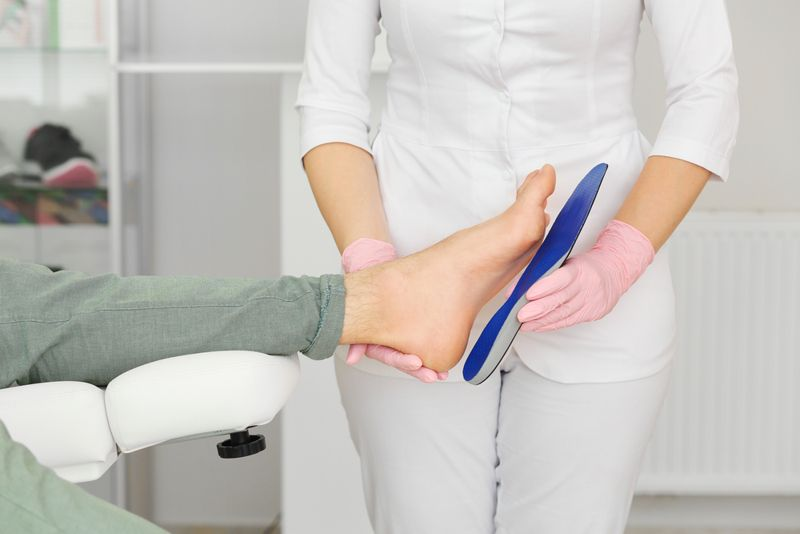 medical practitioner fitting patient for orthotics