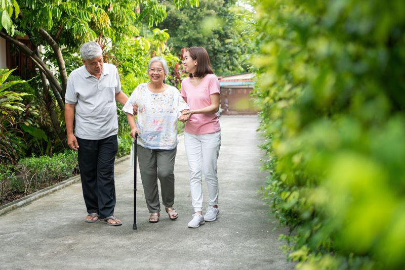 family helping older woman walk with cane in garden