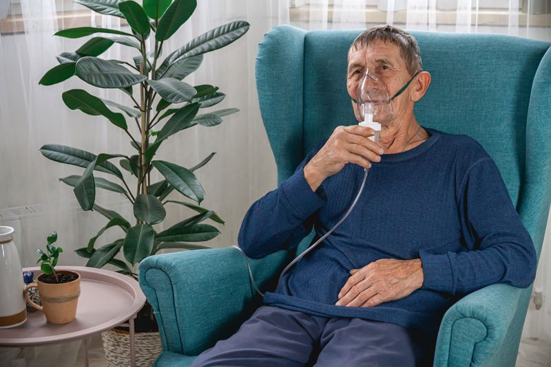 older man at home with an oxygen tank