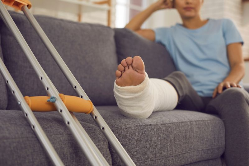 person with foot wrapped in cast resting on couch
