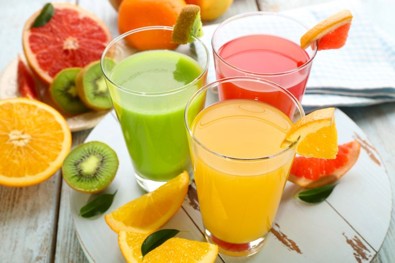 three fruit juices surrounded by fruit slices