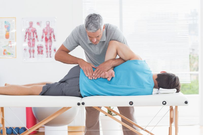 physical therapist working on a patient's back