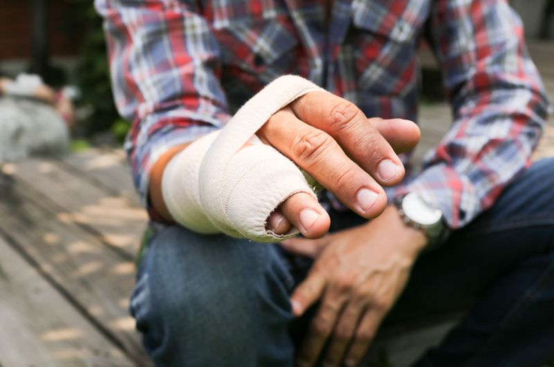 man's injured hand with last two fingers wrapped