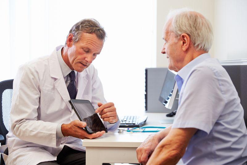 doctor showing elderly patient information
