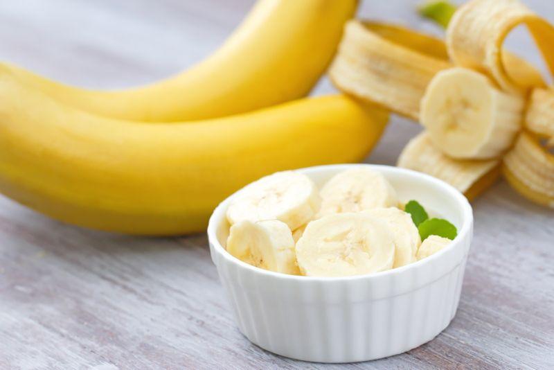 sliced banana with whole bananas behind