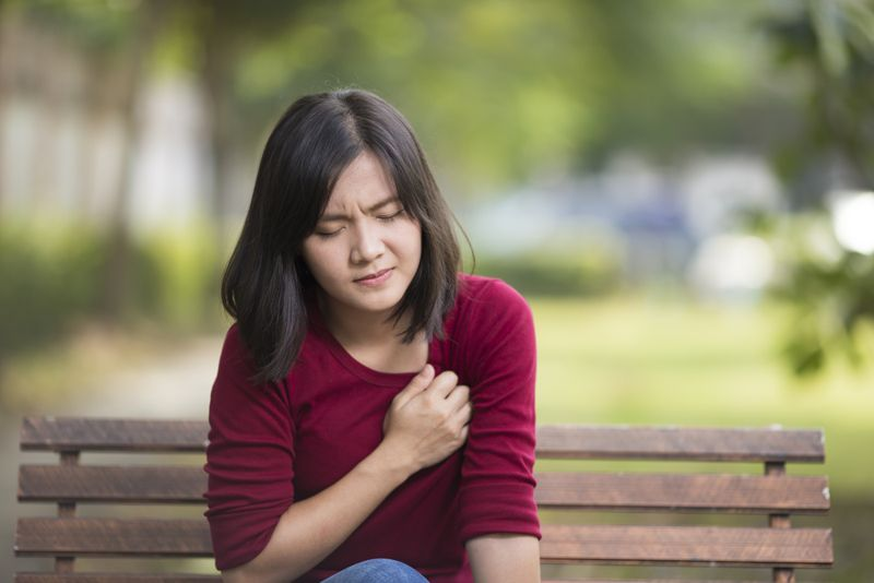 woman having chest pain on a park bench